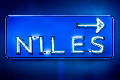 Painted the Niles Sign using spot light with a  blue gel filter.  I processed the raw image twice, once for the sign, then a second time to draw out more exposure to the background, that created the blue glow around the sign.  Also increased noise.    Then combined the two images, added a layer mask then painted through the layer mask to expose the sign.