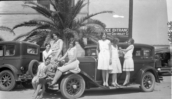 Central Power and Light Employees. Left: Annie Porter. Behind her is Esther Dienst Smith. The woman with the patterned dress is unknown, as is the woman sitting on the fender. Standing women L to R: Lurline Mallard, Lizzie Porter Rose, unknown.