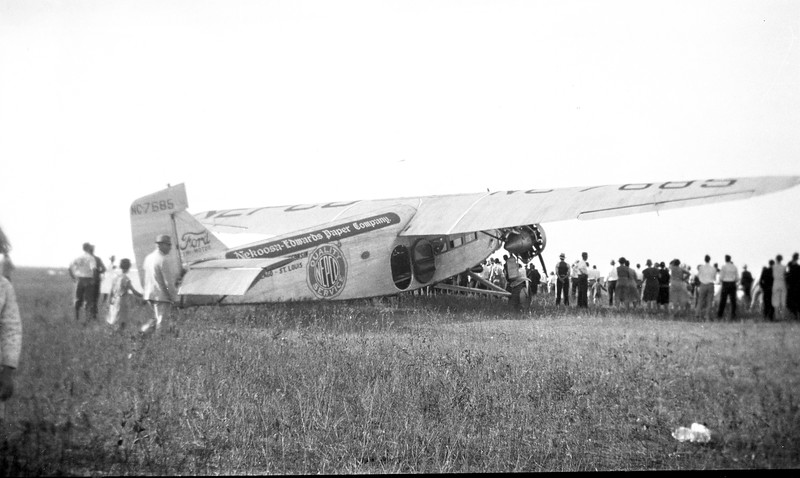 The town turns out to see a Ford Trimotor airplane. Note there is no airport, just a vacant field.