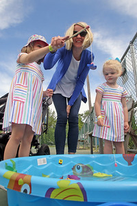 Bridgette Fleming and her daughters Maisy and Elodie take part in a fishing game as Bay Head Elementary School held their Davey Jones Day fun fair that included a water slide, games, food and more on Saturday June 8, 2019. (MARK R. SULLIVAN /THE OCEAN STAR)