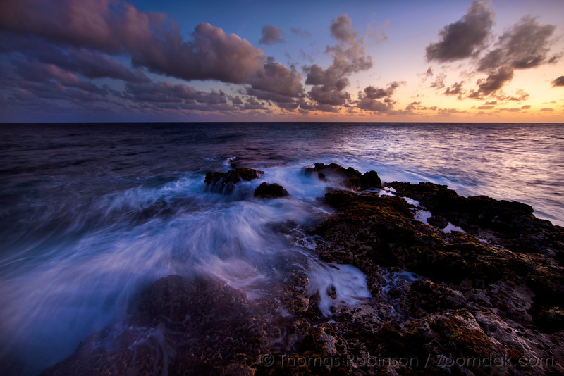 An incoming wave spills over rock at sunset on the west shore of Kauai near Poipu.