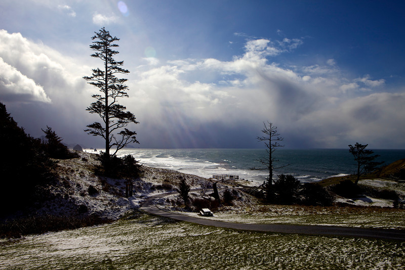 The sun breaks through the clouds on a cold winter day at a snow dusted Ecola Point.