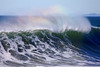 A rainbow catches the horsetails on the back spray of a wave cresting at the the point Seaside, Oregon. This is an internationally known surf spot but hard-core local surfers keep it closely guarded.