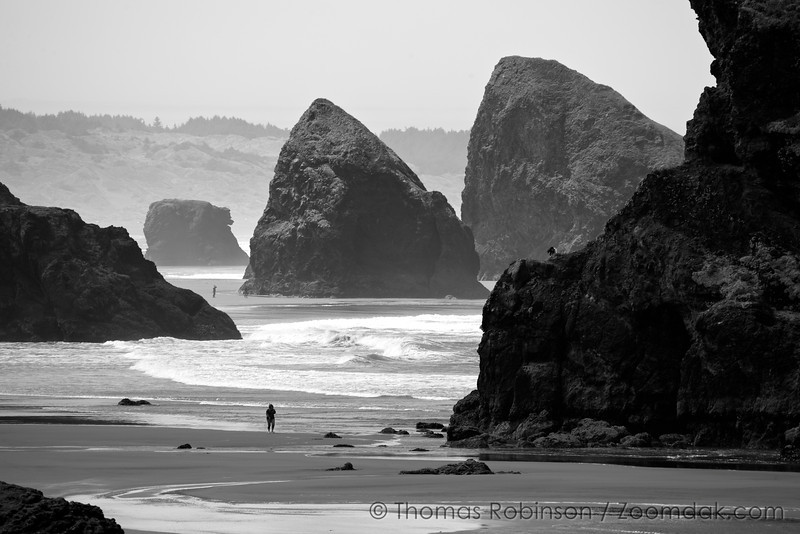 Sea stacks tower above the people along the beach at Cape Sebastian, Oregon. <br /> <br /> Fun game: There are 4 people in this picture. Can you find all of them?