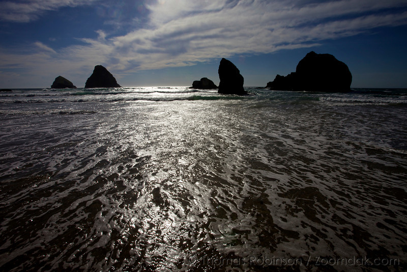 Waves rush into the shore of Oceanside, Oregon mid-day.