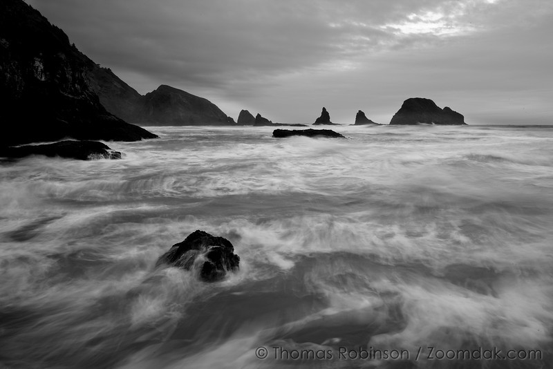 Waves collide with the rocks around Oceanside, Oregon on stormy evening.