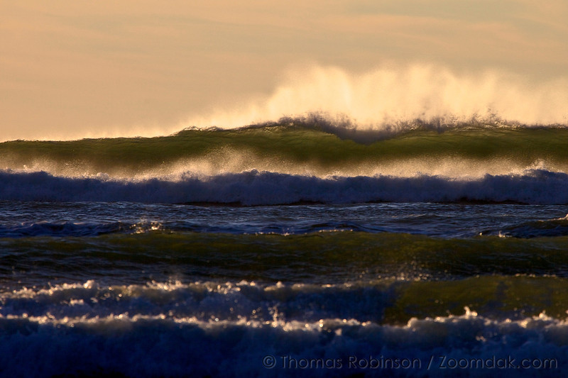 Backlit waves crash onto the shores of the Oregon Coast, marking the edge of the Pacific Ocean.
