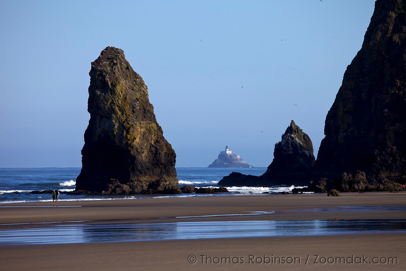 Tillamook Lighthouse (Terrible Tilly) is peeks through the gap between Haystack and one of the needles. One can see the massive size of these rocks by the people walking in the lower left corner.