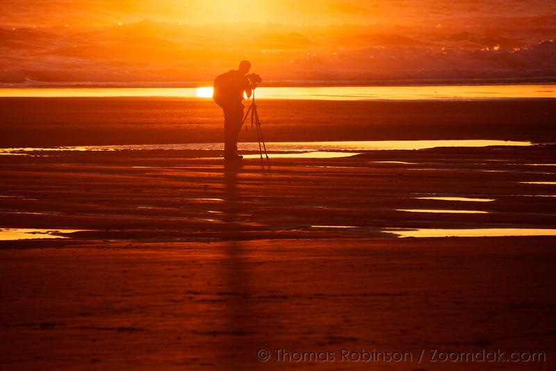 A photographer captures the golden lighting flooding across the beach.