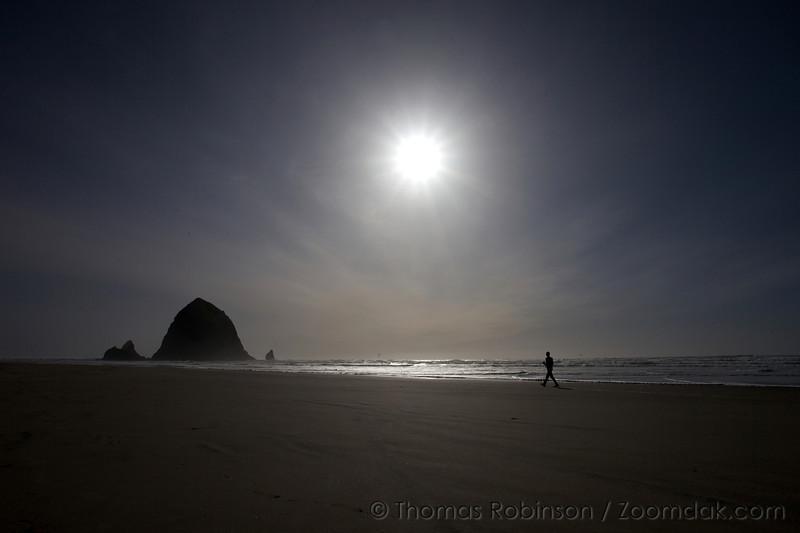 A lone man strolls the shoreline towards Haystack Rock in Cannon Beach, Oregon.