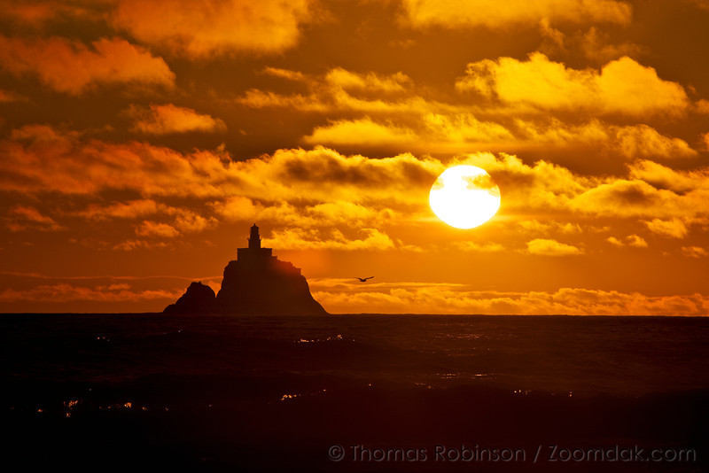 """Tillamook Lighthouse, """"Terrible Tilly"""" stands silhouetted at sunset with the full disc of the sun glowing above it. <br /> <br /> Tillamook Lighthouse was first lit on January 21st, 1881. Deactivated in 1957, it now serves as columbarium. <br /> <br /> For more information see: <a href=""""http://www.rudyalicelighthouse.net/NWLts/Tillamk/Tillamk.htm"""">http://www.rudyalicelighthouse.net/NWLts/Tillamk/Tillamk.htm</a>"""