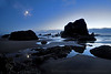 The moon glows in the low tide twilight tidepools of Ecola beach.