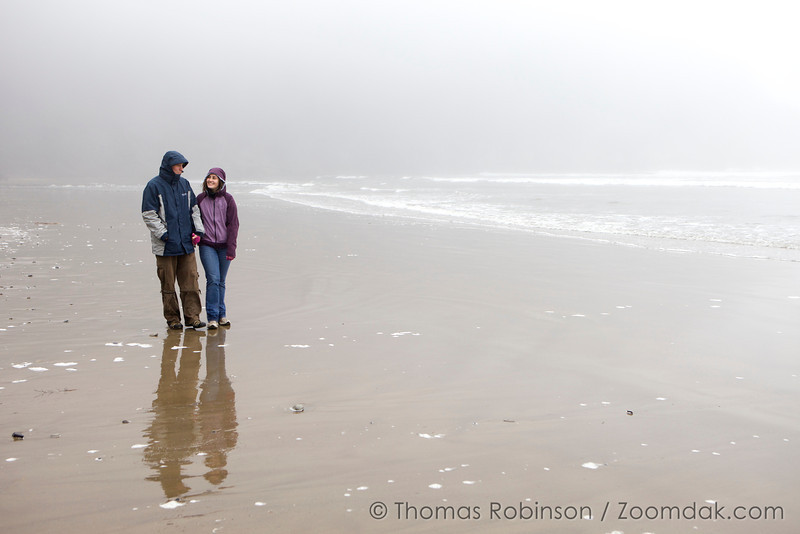 Jared and Merrie Albright stroll down Shortsands Beach in the fog.