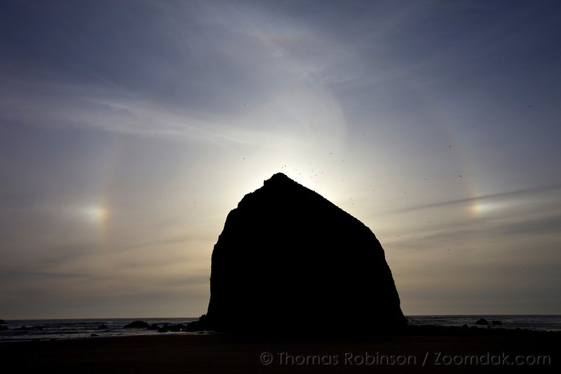 A weather phenomenon known as a sun dog or parhelion arches over Haystack Rock. The luminous halo is created when sunight is refracted through cold and high cirrus clouds.