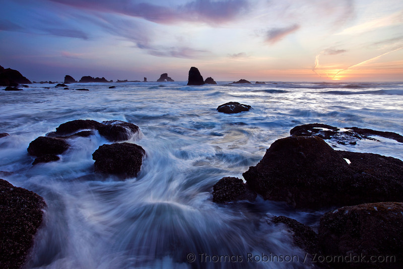 A slow exposure shows the motion of waves at sunset around the rocks south of Indian Beach.