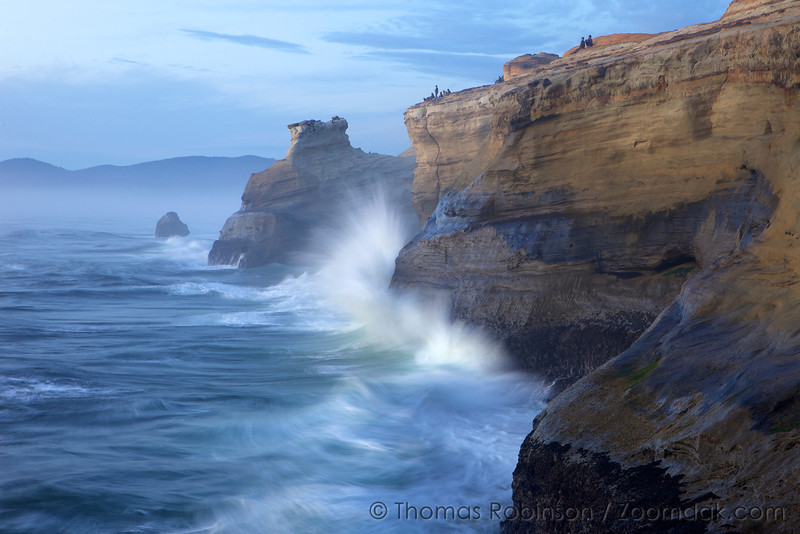 Waves crash into the cliffs of Cape Kiwanda as people sit far above.