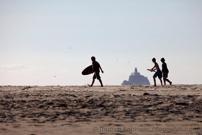 Three teenagers walk across the beach headed to go skimboarding with Tillamook Lighthouse in the background.