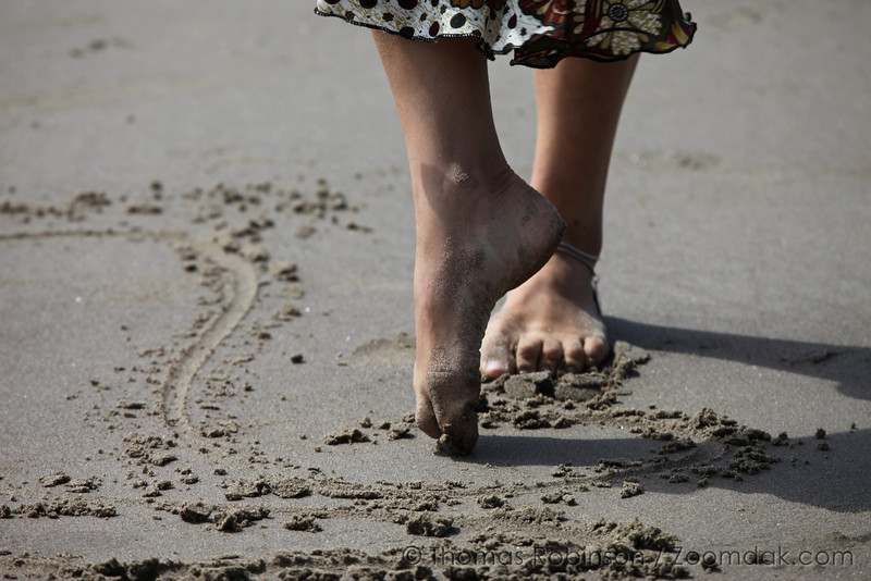 Michelle Hammer doodles gracefully in the sand like a ballerina with her feet.