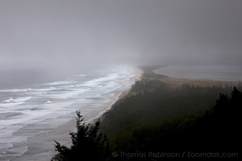 Fog covers most of the overlook from Anderson's Viewpoint in Cape Lookout State Park with the the Pacific Ocean, Netarts Spit and Netarts Bay peeking through. The three rocks of Oceanside can also barely be seen through the fog.