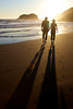 Jared and Merrie Albright, a romantic couple walk hand in hand into the sunset in Cannon Beach, Oregon.
