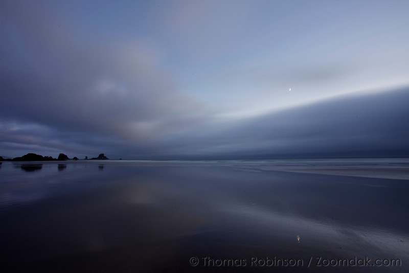 The crescent moon glows above the evening clouds of Indian Beach in Ecola State Park.