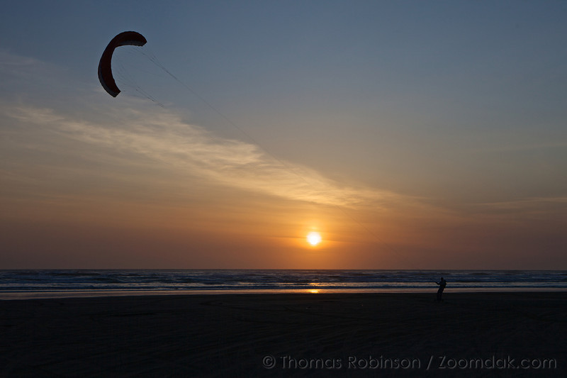 A person kite-boards at sunset at Sunset Beach in Gearhart, Oregon. Kite-boarding is a sport the combines being pulled a giant kite and riding on a large skateboard.