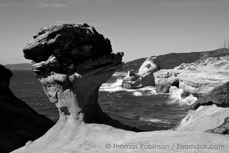 An odd rock formation rises above the surrounding sandstone in Cape Kiwanda, Oregon.