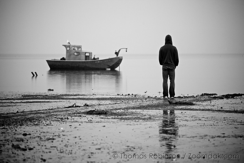 Matt Park looks across Tillamook Bay, engulfed in the silent evening. A seagull perches on a boat.
