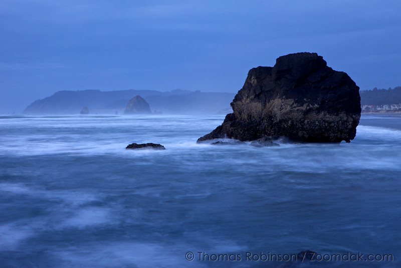 Waves wash amidst the rocks around Lady Rock south of Cannon Beach with Haystack poking up in the distance.