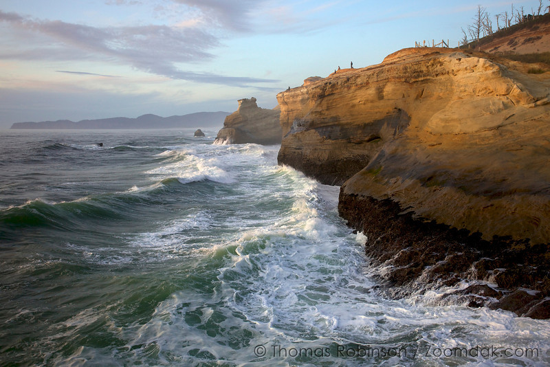 People enjoy the sunset as waves crash into the cliffs of Cape Kiwanda in Pacific City, Oregon.