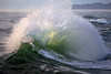 The backwash of one wave collides with the incoming wave creating a dramitic wate explosion. Waves crash into each other.