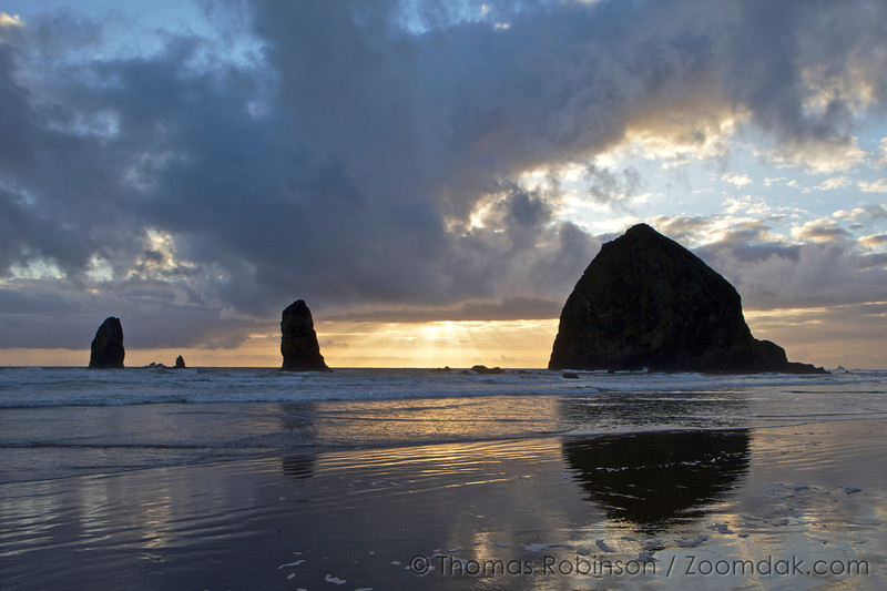 God beams (crepuscular rays) break through the clouds over Haystack Rock in Cannon Beach, Oregon.