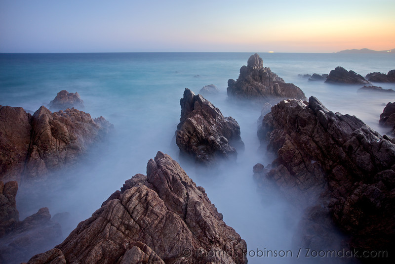 A slow exposure makes the flow of waves look like fog through the rocks in Baja, Mexico.