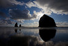 The sun breaks over the edge of Haystack Rock silhouetted in Cannon Beach.
