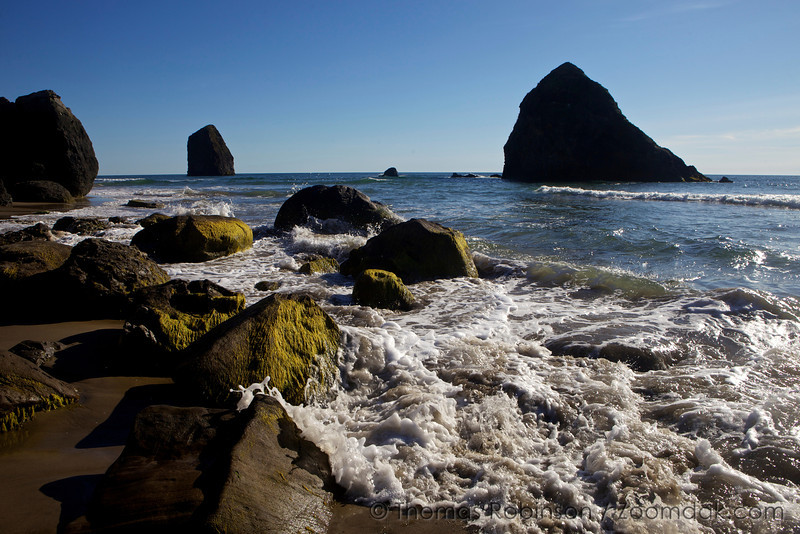A wave rolls into the rocks of Silver Point at the south end of Cannon Beach.