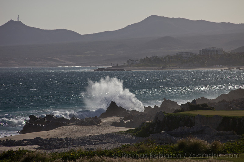 A backlit wave crashes over rocks along the shore of the Baja Peninsula.