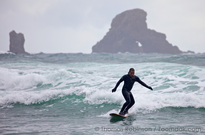 A surfer rides a small wave in on an overcast day at Indian Beach.