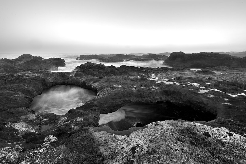 An incoming wave flows under two arches at sunrise in Yachats State Park.