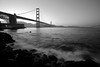 The Golden Gate Bridge stands iconic in black and white from Fort Point in Presidio of San Francisco.