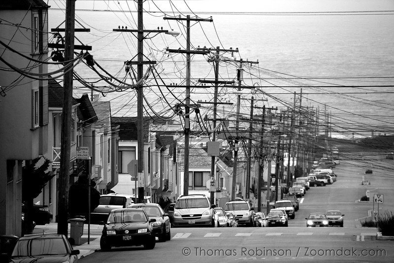 Looking down the a hill in San Francisco, one can see powerlines leading into the ocean below.