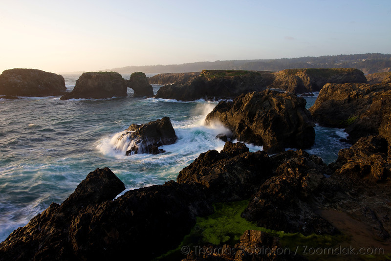 Waves crash against the sea stacks of Mendocino Headlands State Park at sunset in Mendocino, California.