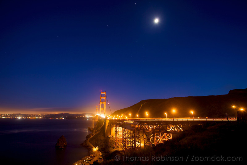 The moon shines high above the Golden Gate Bridge during twilight in San Francisco.