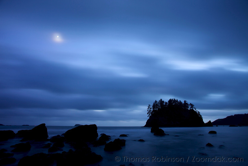 The moon shines through clouds rolling across the sky above the beach at Trinidad State Park.