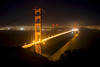 A slow exposure shows the light streaks of cars across the iconic Golden Gate Bridge at night.