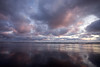 Clouds reflect off the sand at sunset in Cannon Beach.