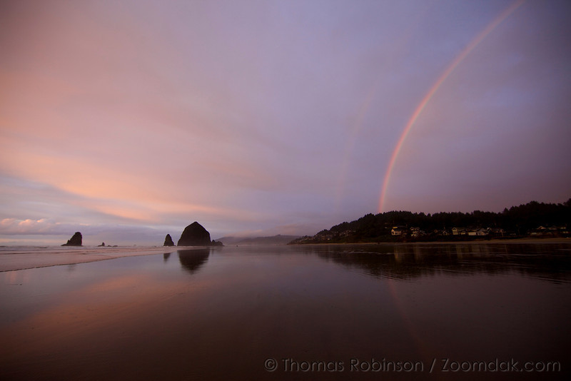 A rainbow shines down upon Cannon Beach looking north at Haystack Rock and the needles.