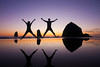 Jump for joy! <br /> Two silhouettes leap with arms outstretched at sunset at Haystack Rock in Cannon Beach, Oregon