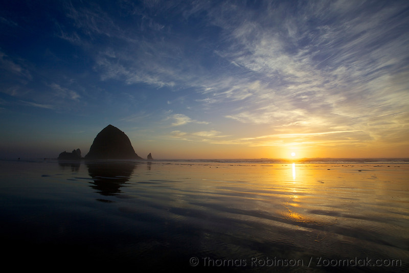 Cirrostratus clouds hang high above Haystack Rock as the sun sets over the ocean in Cannon Beach, Oregon.