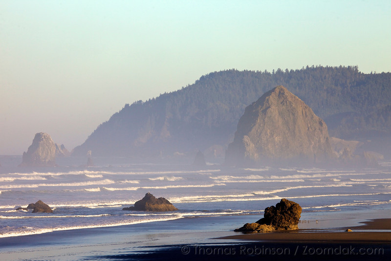 Morning light spills onto Haystack Rock, the needles and Lady Rocks in Cannon Beach, Oregon.