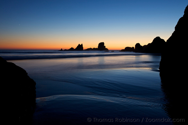 A single star sings out in the sky about silhouetted rocks during the twilight glow at Crescent Beach in Ecola State Park, Oregon.